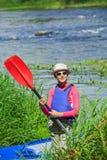 Fille près d'un kayak sur la rivière Photographie stock