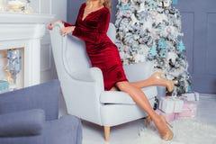 Fille près de l'arbre de Noël dans les chaussures à talons hauts dans le dre rouge photos stock