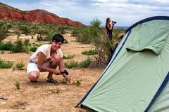Fille près de la tente sur un fond des montagnes Photos stock