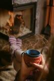 Fille près de situer la cheminée avec une tasse bleue Photo stock