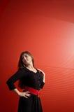 Fille près du mur rouge Photographie stock