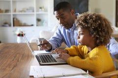 Fille pré de l'adolescence d'Afro-américain de fille à l'aide d'un ordinateur portable se reposant à la table dans la salle à man photographie stock libre de droits