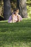 Fille précieuse d'ittle dans la robe rose sur l'herbe Image stock