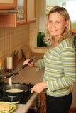 Fille préparant des crêpes. Image stock