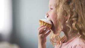 Fille préscolaire pâle mignonne mangeant le gâteau crémeux et souriant, friandise à la partie photos libres de droits