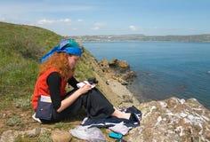 Fille prenant des notes sur la plage Image libre de droits