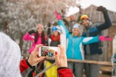 Fille prenant des photos des amis heureux le jour froid d'hiver Photographie stock libre de droits