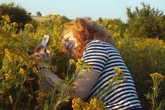 Fille prenant des photos des fleurs à un téléphone portable images libres de droits
