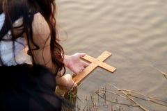 Fille prenant la croix en bois de la rivière photographie stock