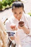 Fille prenant la photo de son ami avec des petits gâteaux Image libre de droits