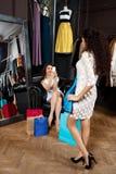 Fille prenant la photo des autres essayant sur la robe dans le mail Photos libres de droits