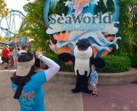 Fille prenant la photo du gentil garçon avec le caractère de baleine au parc à thème de Seaworld image stock