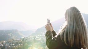 Fille prenant la photo du paysage urbain de paysage à partir du dessus de montagne au téléphone intelligent de cellules, touriste banque de vidéos