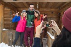Fille prenant la photo sur la station de vacances en bois de neige d'hiver de Chambre de montagne de pays de téléphone de groupe  Images libres de droits