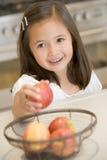 Fille prenant la pomme du panier de fruit à la maison Image libre de droits