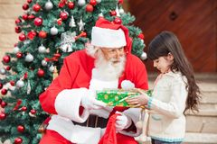 Fille prenant le cadeau de Santa Claus Photos stock