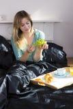 Fille prenant le petit déjeuner dans le lit photo stock