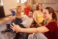 Fille prenant le selfie avec des amis dans le studio de forme physique Image stock