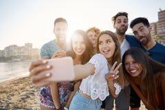 Fille prenant le selfie avec des amis faisant le signe de paix Photo libre de droits