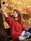 Fille prenant le selfie de photo d'individu avec l'appareil-photo de smartphone dehors Image stock