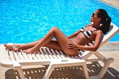 Fille prenant un bain de soleil et regardant à la piscine Photos stock