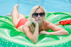 Fille prenant un bain de soleil sur gonflable Photo libre de droits