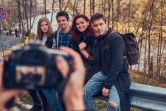Fille prenant une photo de ses amis Groupe de jeunes amis s'asseyant sur la rambarde près de la route image stock