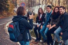 Fille prenant une photo de ses amis Groupe de jeunes amis s'asseyant sur la rambarde près de la route images stock