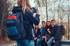 Fille prenant une photo de ses amis Groupe de jeunes amis s'asseyant sur la rambarde près de la route photographie stock