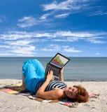 Fille presque travaillant sur l'ordinateur portatif de la mer Images stock