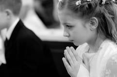 Fille priant dans l'église Photographie stock