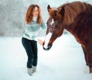 Fille principale rouge avec un cheval dans un domaine de neige en hiver images libres de droits