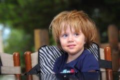 Fille punie dans une chaise dans des cours d'été Image libre de droits