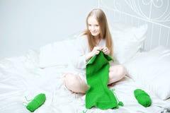 Fille qui tricote sur les pointeaux Image stock