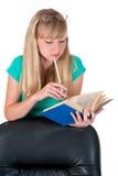 Fille réfléchie avec un crayon et le livre de Photographie stock libre de droits