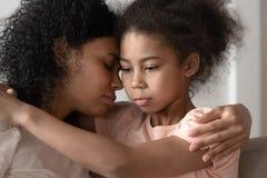 Fille réfléchie d'enfant d'afro-américain embrassant la liaison de maman caressant photographie stock