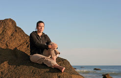Fille réfléchie sur une plage rocheuse Photo libre de droits