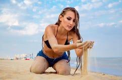 Fille répandant le sable par ses mains Images stock