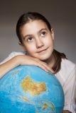 Fille rêvante avec le globe bleu Image libre de droits