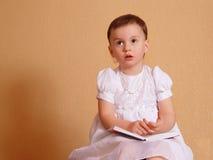 Fille rêvante dans une robe blanche Photographie stock