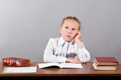 Fille rêveuse d'enfant apprenant au bureau photographie stock