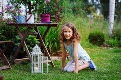 Fille rêveuse heureuse d'enfant jouant dans le jardin d'été, décoré de la lumière de lanterne et de la bougie Photographie stock
