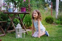 Fille rêveuse heureuse d'enfant jouant dans le jardin d'été, décoré de la lumière de lanterne et de la bougie Image stock