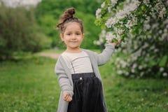 Fille rêveuse heureuse mignonne d'enfant d'enfant en bas âge marchant dans le jardin de floraison de ressort, célébrant Pâques ex photos libres de droits
