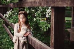 Fille rêveuse mignonne d'enfant posant à la barrière en bois rustique avec l'ours de nounours Images libres de droits