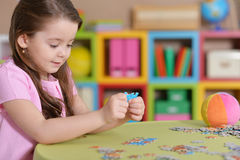 Fille rassemblant des puzzles Photographie stock libre de droits