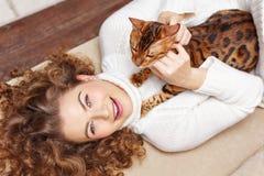 Fille rayant le chat se trouvant sur le sofa étreintes Images libres de droits