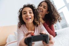 Fille rayonnante jouant des jeux vidéo à la maison Images stock