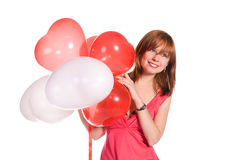 Fille Red-haired dans une robe rose avec des ballons Image stock