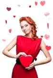 Fille red-haired de sourire retenant le coeur rouge Photos stock